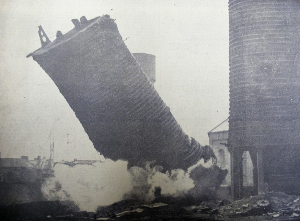The southernmost of the Summerlee blast furnaces being brought down by gelignite in 1938