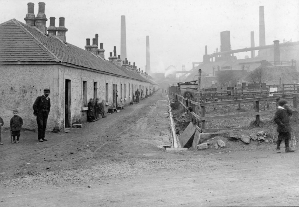 This photograph from 1910 gives an idea of the conditions Lanarkshire ironworkers lived in. This is Furnace Row, Wishaw. Off camera to the left a railway line runs right past the back of these houses.