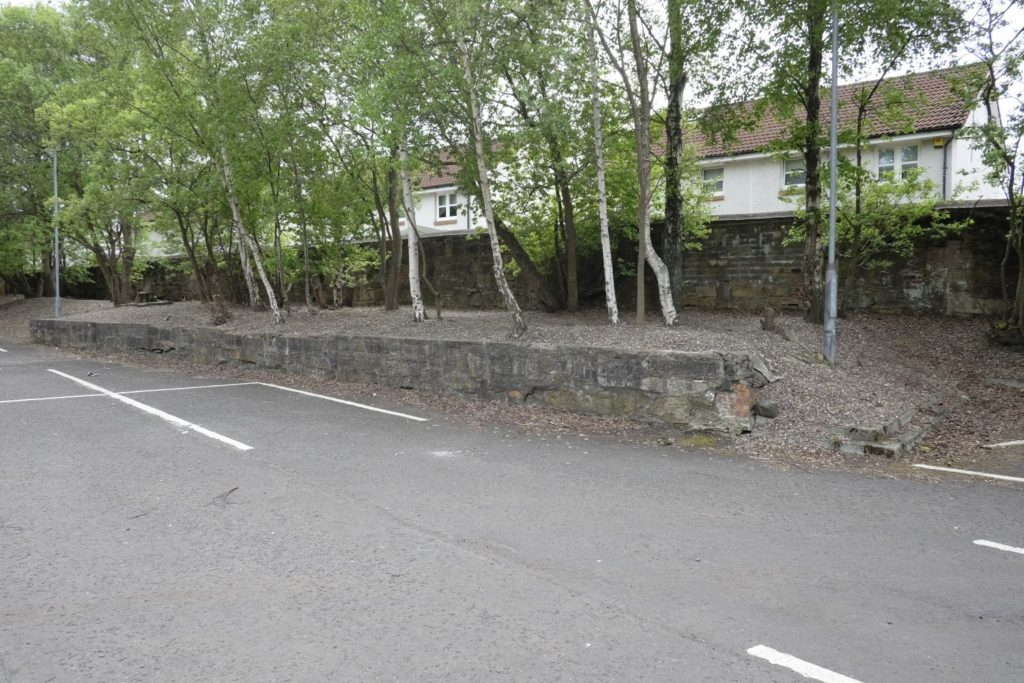 Remains of a railway goods station platform in the supermarket car park on the site of the Coatbridge Hole. May 2019.