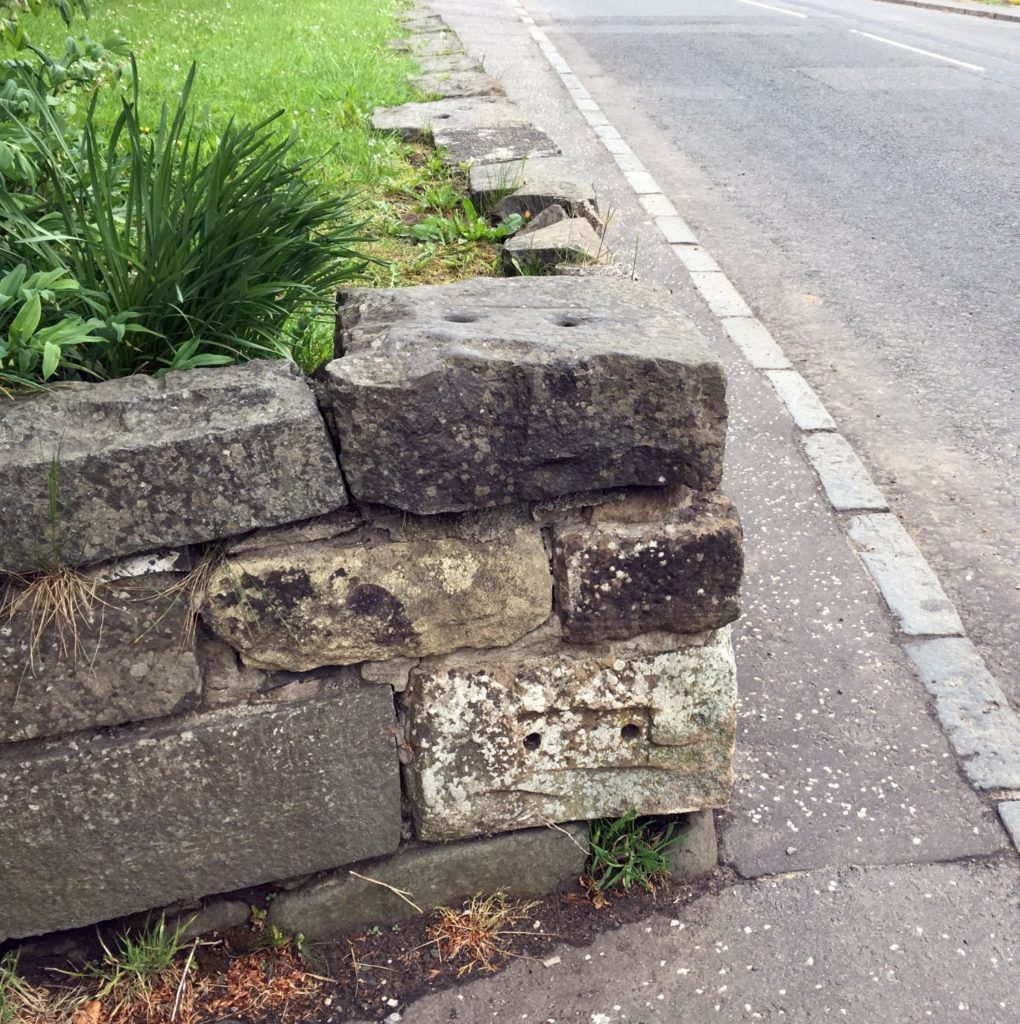 At the spot where the Monkland and Kirkintilloch Railway once crossed Glenboig Main Street you can see old stone sleepers built into a roadside wall. The holes are where the metal shoes that held the rails were fixed with iron pins.