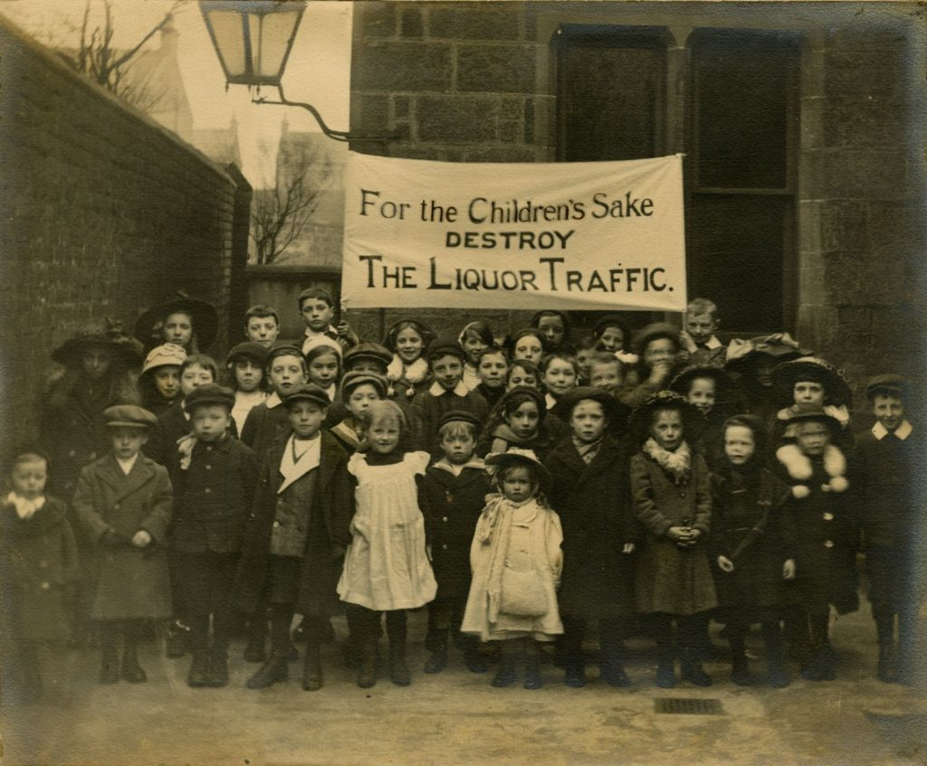 "St Thomas Wesleyan Methodist Church Band of Hope, 1910s with banner proclaiming ""For the Children's Sake, Destroy the Liquor Traffic."""