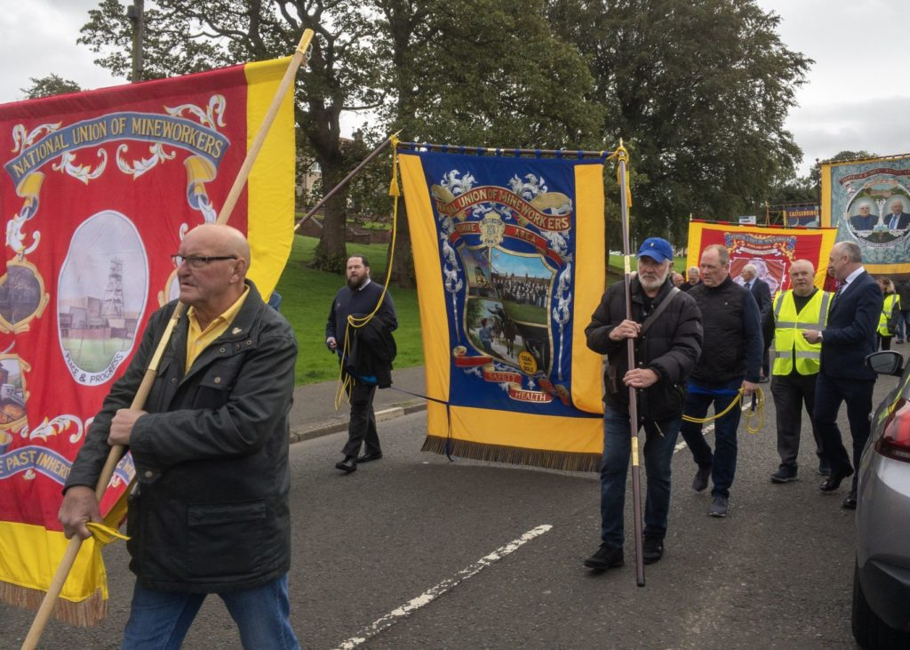 Trades union banners displayed on a march to mark the 60th anniversary of the Auchengeich disaster.