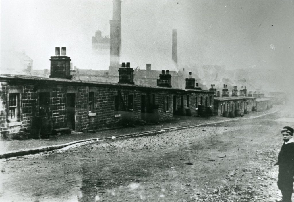 The workers' housing of Flat Row on the east side of Benhar Road with the Shotts Iron Works in the background.