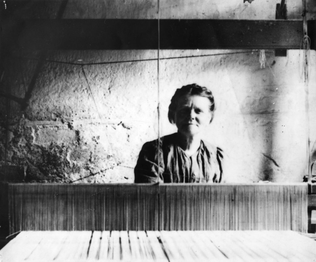 Betsy, a handloom weaver at her loom, around 1898.