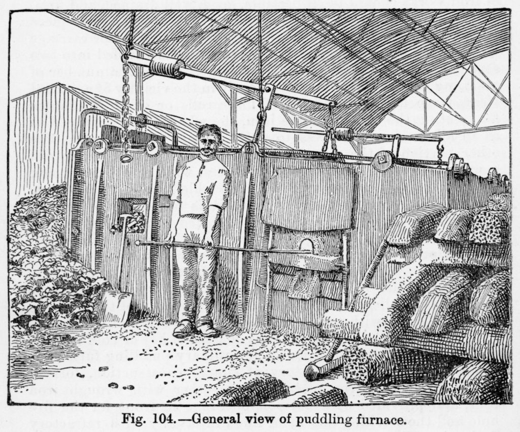 Illustration of a puddler and his furnace with pig iron stacked up beside it from 'The Metallurgy of Iron' by Thomas Turner, 1920. The man is holding his 'raddle', a long iron rod with a hook on the end for stirring the mass of molten iron.