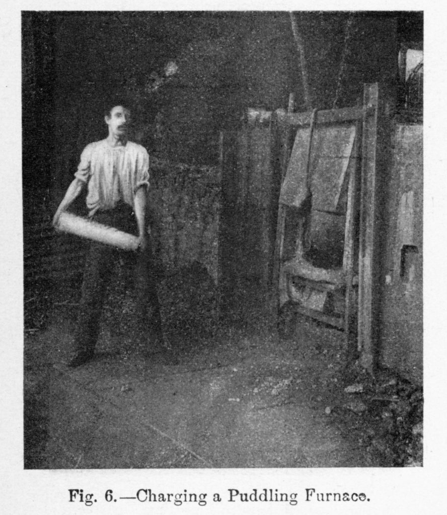 Charging a puddling furnace: this puddler is lifting a cast iron 'pig' ready to put it into the furnace.