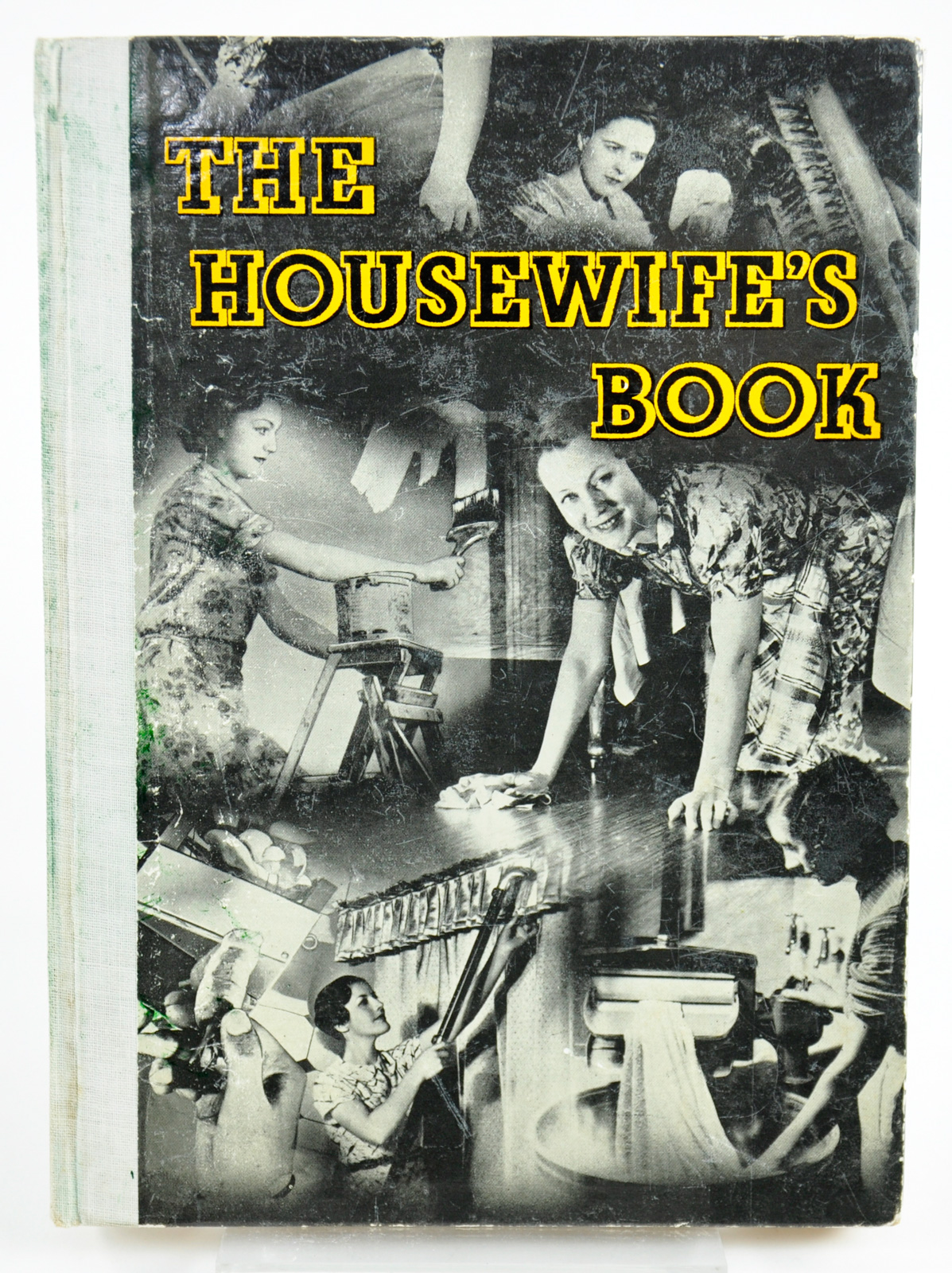 The Housewife's Book, around 1925-30. The front cover is a montage of black and white photos of women doing various housework tasks, including scrubbing the floor and using a clothes wringer.