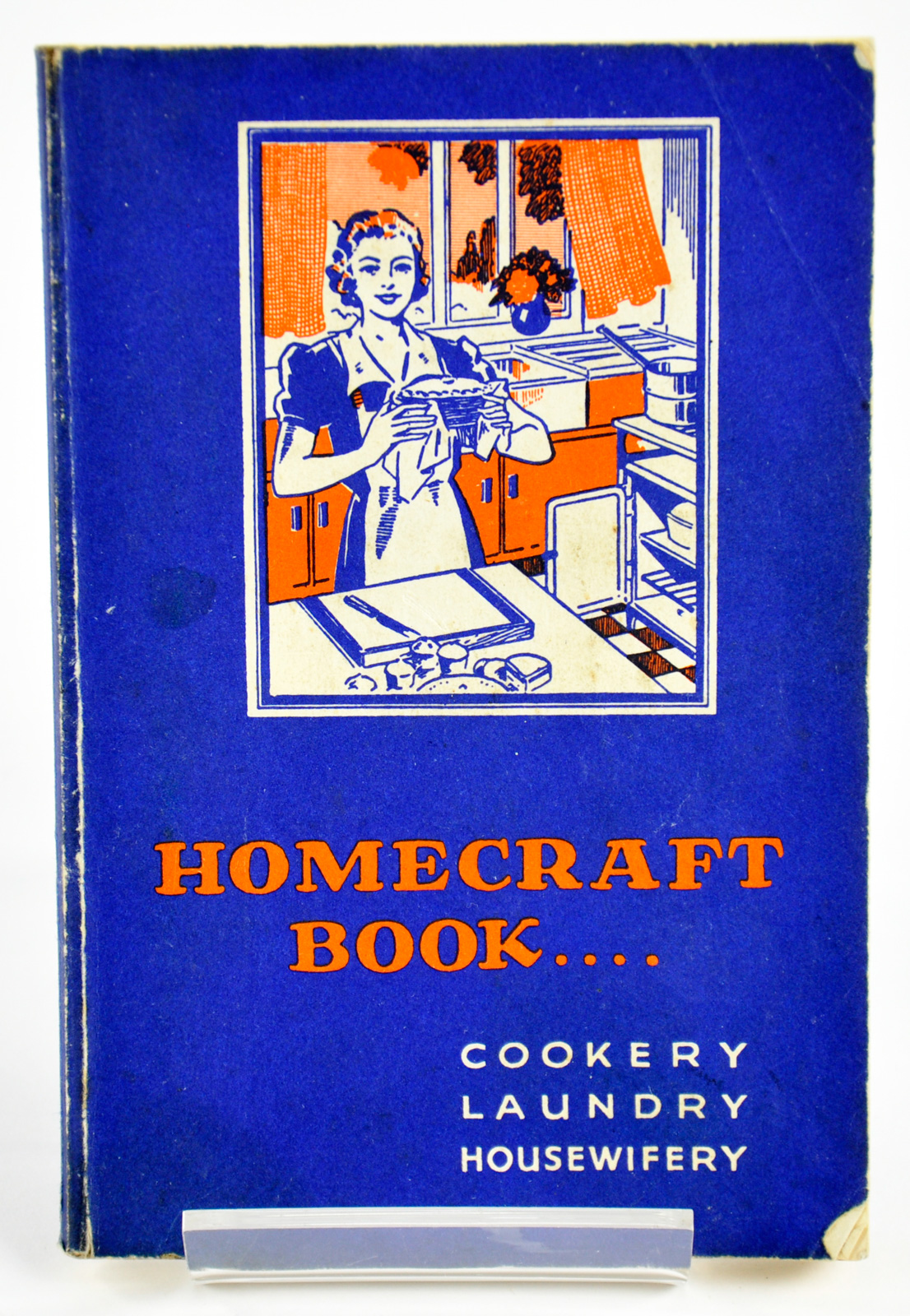 Homecraft Book: Cookery, Laundry, Midwifery, 1930s, depicting a sketch of a woman baking in the kitchen on the front cover