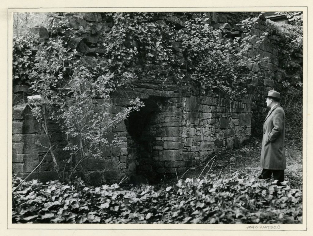 Black and white photograph of a man in coat and hat standing in front of a large ruined wall covered in foliage