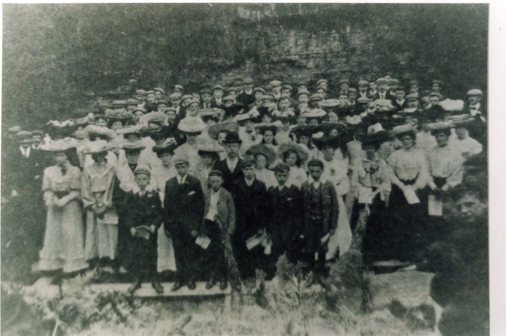 Black and white photograph of a large group of men, women and children, mostly wearing hats, c.1900