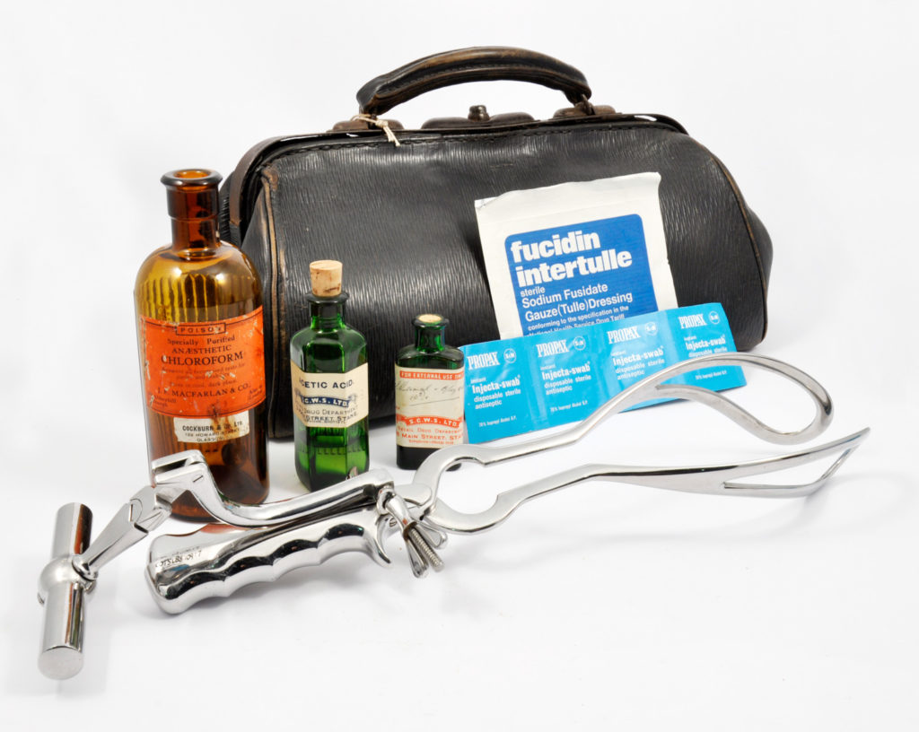 A leather Gladstone bag with medical implements and glass bottles