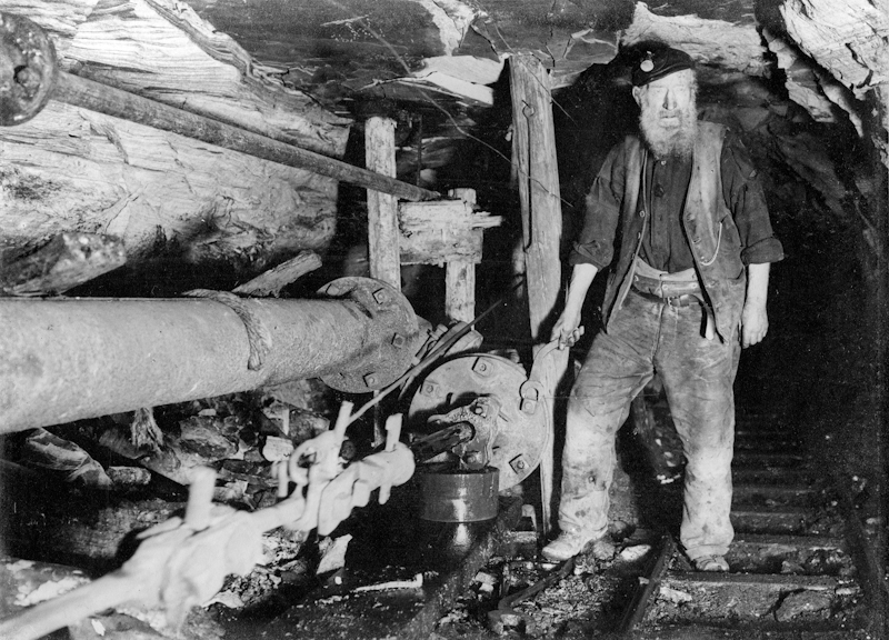 An engineer maintains a crank pump underground in Camp Colliery near Motherwell, around 1910.