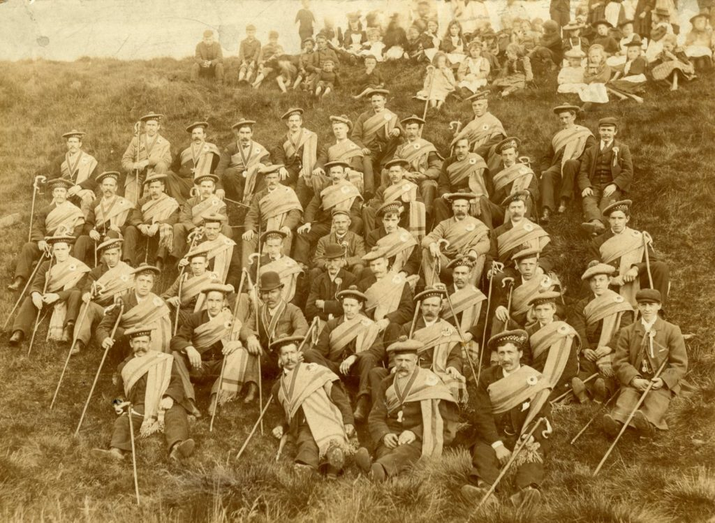 Sepia toned photograph of a large group of men sitting on a hillside dressed in bonnets and plaids and holding shepherds crooks. A smaller group of women and children can be seen above them.