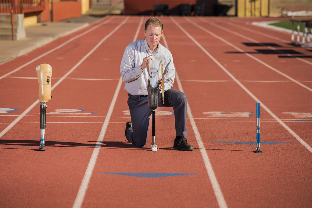 Photo of a man kneeling on a running track, holding a prosthetic leg and flanked by two others