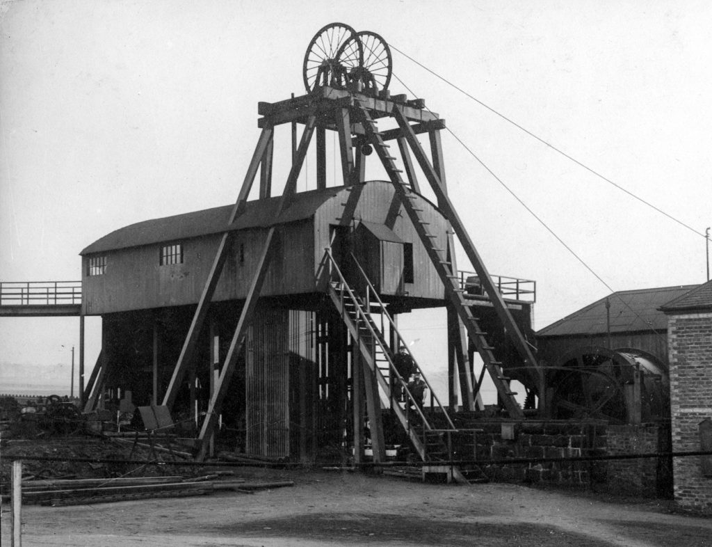Pit head winding gear at Camp Colliery near Motherwell around 1910. The brick building on the right houses the winding engine and the shaft is directly below the wheels of the head gear.