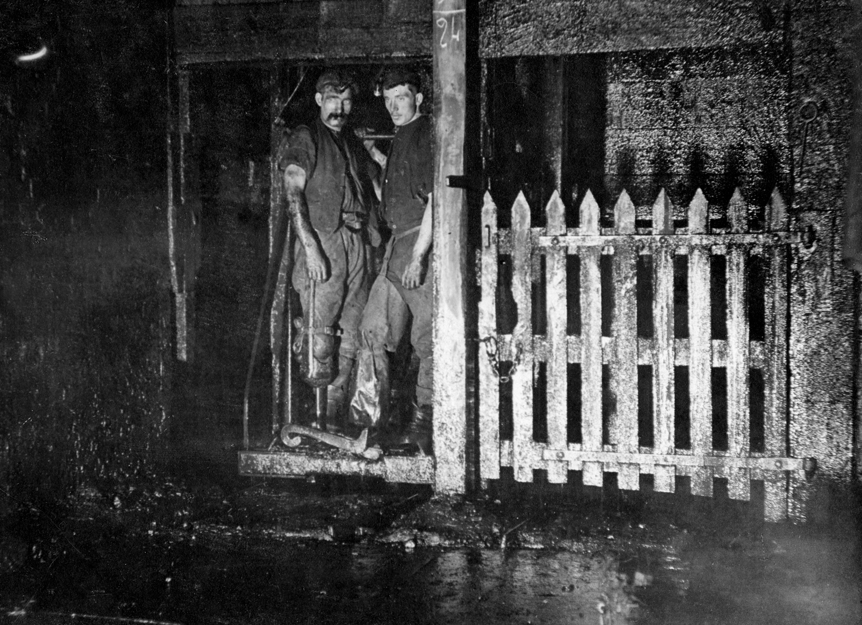 Two miners in a cage underground waiting to ascend to the surface at Camp Colliery, around 1910. The gate on the right shows that this isn't the bottom level of the pit - it goes further down.