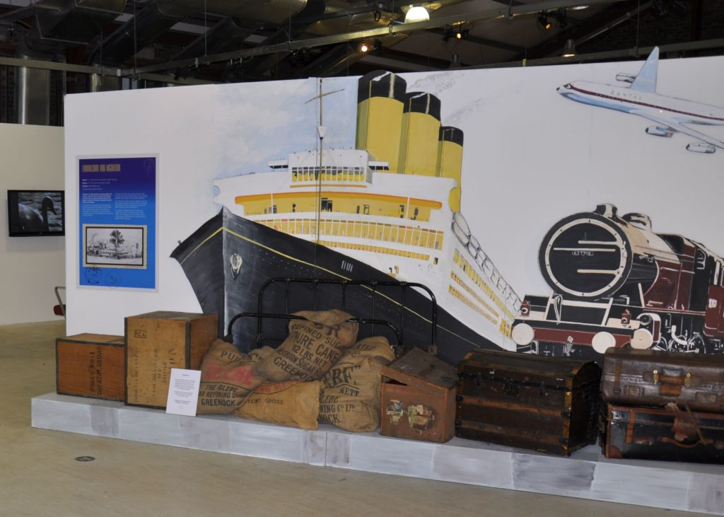 An exhibition set display of trunks, suitcases, crates and sugar sacks against the backdrop of a mural featuring a transatlantic liner, steam train and aeroplane