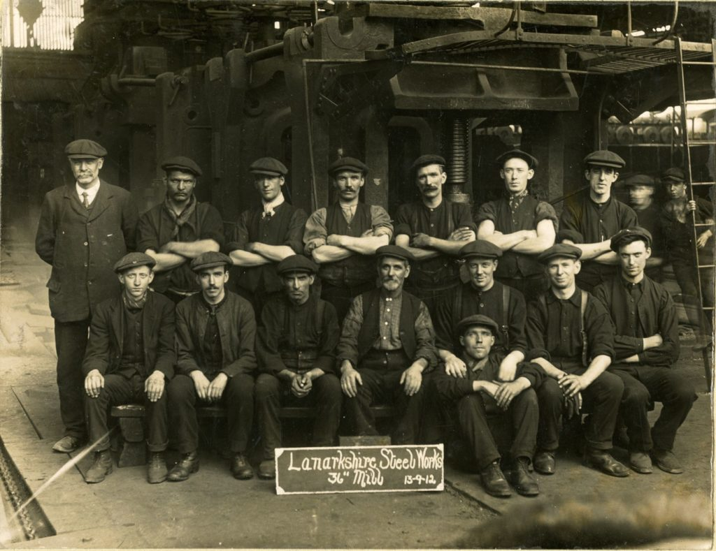 A rolling mill team at the Lanarkshire Steel Works, 1912. The metal plating on the ground is to protect the floor from the red-hot steel as it emerges from the mill rollers.